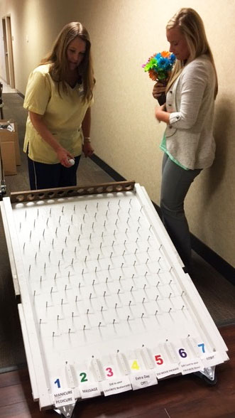Cheri July star employee recipient playing plinko for prizes