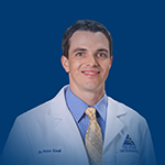 Dr. Peter Knoll General Orthopaedics Joint Replacement white coat headshot blue background